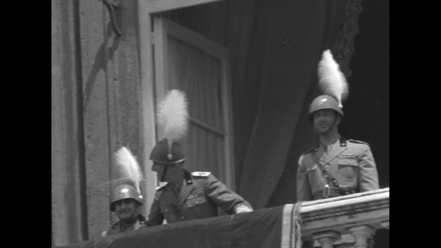 king victor emmanuel iii and prince humbert wearing feathered helmets appear at draped balcony of the royal palace of naples / vs large crowd with... - プレビシート広場点の映像素材/bロール