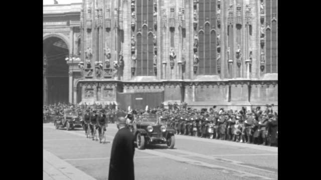 king victor emmanuel iii motorcade and police on bicycles drive past crowd as they move through the piazza del duomo with the arched entrance to the... - galleria vittorio emanuele ii stock videos and b-roll footage