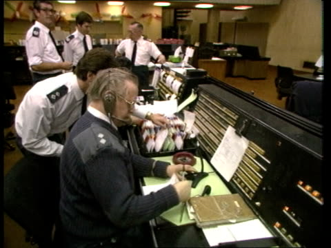 vídeos y material grabado en eventos de stock de ambulance service; b) int england: london: central ambulance control: tcms side male telephonist seated switchboard? & working as group fire officers... - centralita de teléfono