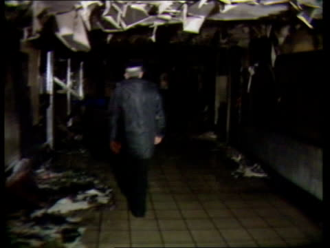 king's cross fire inquiry fire sprinklers and extinguishers not used tx 191187 king's cross station bv policeman away along charred corridor track - キングスクロス駅点の映像素材/bロール