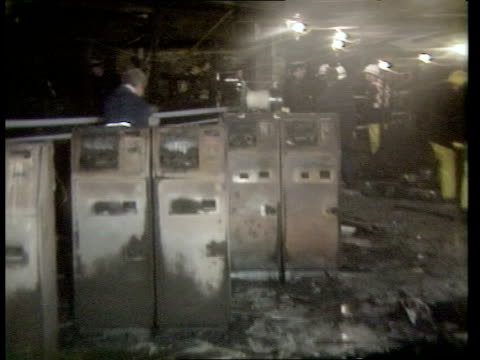 King's Cross Tube fire Events a London King's Cross Station MS Firemen police standing in charred main ticket hall PAN RL burnt ticket machines PULL...