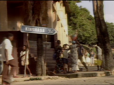 1989 VS Kinshasa directional sign on busy city street in Zaire tracking shot from windshield of car as it drives on road through savanna in Republic...