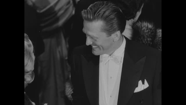vídeos de stock e filmes b-roll de kirk douglas peggy cummins talking waiting for the arrival of the british royal family at the empire theatre for the annual motion picture show for... - kirk douglas actor