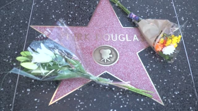 vídeos de stock e filmes b-roll de kirk douglas's hollywood walk of fame star is decorated with flowers as fan pay tribute to the legendary actor - kirk douglas actor