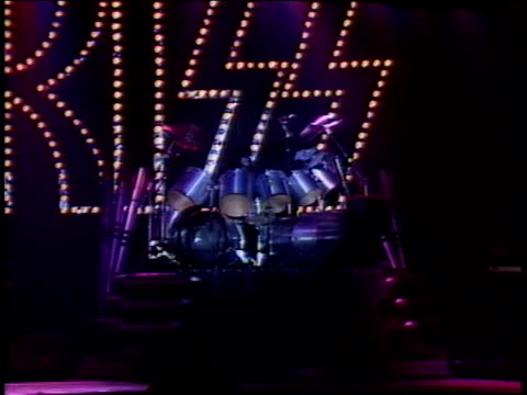 vídeos de stock e filmes b-roll de kiss on their new stage for the creatures of the night tour eric carr demonstrates his drum set shaped like the turrent of a tank and emitting smoke... - música heavy metal