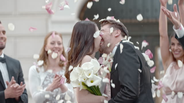 slo mo kissing newlyweds being showered with rose petals - bouquet stock videos and b-roll footage