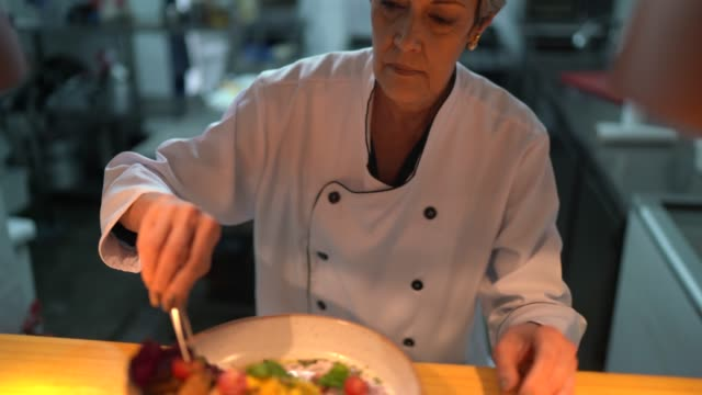 vidéos et rushes de chef de cuisine utilisant des pincettes pour finaliser un plat - cuisinière