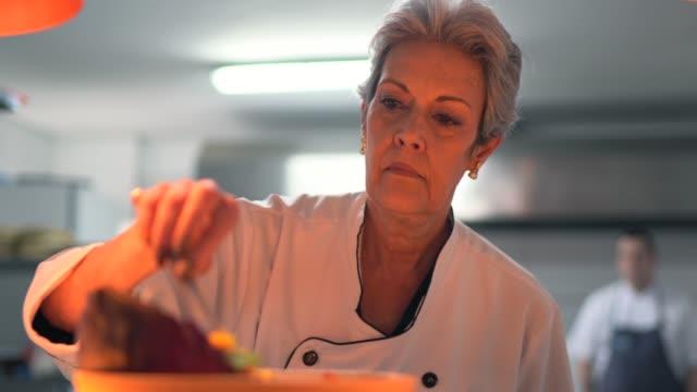 vídeos de stock, filmes e b-roll de cozinheiro chefe da cozinha que usa pinças para finalizar um prato - chef de cozinha