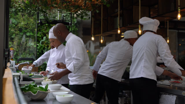 kitchen crew working fast at the restaurant preparing meals - ristorante video stock e b–roll