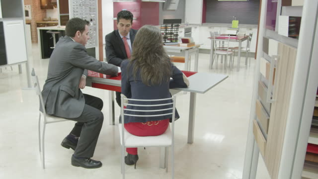 ts ws  kitchen salesman and young couple seated at desk discussing plans - strategia di vendita video stock e b–roll