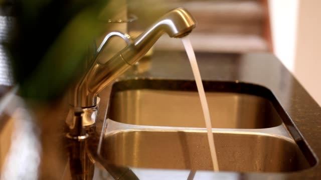 vídeos de stock e filmes b-roll de kitchen sink faucet running water pan. - lava loiças