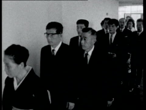 kitchen staff preparing wedding food / bride and groom and guests walking along corridor to wedding hall in department store / notices for weddings /... - 1964年点の映像素材/bロール