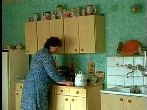 vidéos et rushes de 1994 montage ms kitchen stove/ ms woman at kitchen counter placing glasses onto tray/ ms father, mother and son at dining table/ poland/ audio - placard