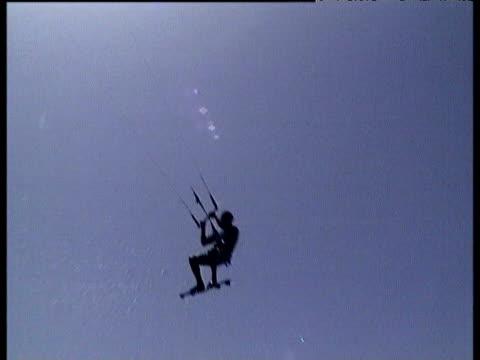 kite boarder surfs and leaps into air silhouetted by sun fuerteventura - eskapismus stock-videos und b-roll-filmmaterial