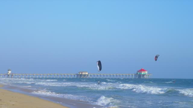 kite surfers sail above huntington beach, california. - huntington beach california stock videos and b-roll footage