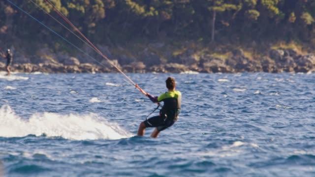 stockvideo's en b-roll-footage met slo mo kiteboarder surfen in de baai - windsurfen