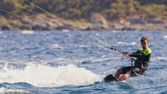 stockvideo's en b-roll-footage met slo mo kiteboarders en windsurfers surfen in de baai - windsurfen