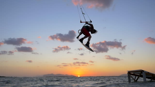 Kiteboarding and riding a kite board off a ramp to jump at sunset. - Slow Motion