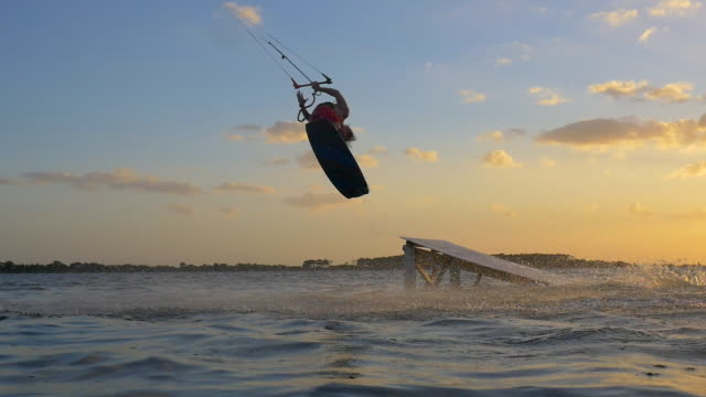 kiteboarding and riding a kite board off a ramp to jump at sunset. - slow motion - goodsportvideo stock videos and b-roll footage