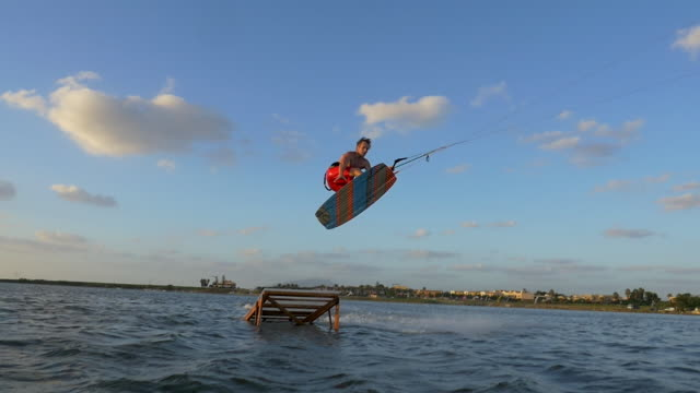 kiteboarding and riding a kite board off a ramp to jump. - slow motion - goodsportvideo stock videos and b-roll footage