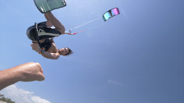 kiteboarding man gives a fist bump on a kite board near a beach. - one mid adult man only stock videos & royalty-free footage