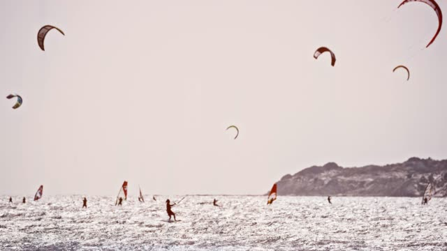 slo mo kiters and windsurfers on a sunny day - adventure stock videos & royalty-free footage