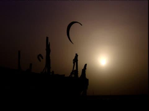 vídeos de stock, filmes e b-roll de kites fly silhouetted on sandy beach at sunset dubai - pipa brinquedo