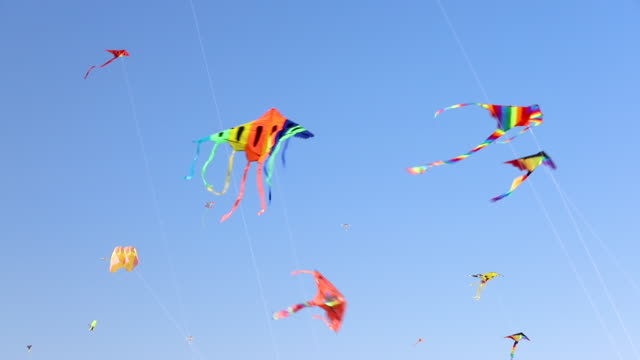 kites flying against but sky - hobbies stock videos & royalty-free footage