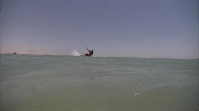 a kitesurfer cuts back and forth across the water under his parachute. - under her feet stock videos & royalty-free footage