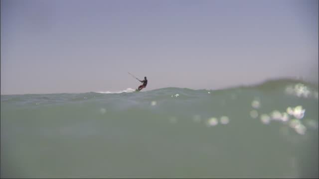 vidéos et rushes de a kitesurfer glides across the water and jumps into the air off a wave. - harnais de sécurité