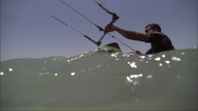 a kitesurfer inserts his feet into bindings on the surfboard while holding the parachute handle, and then takes off across the water. - safety harness stock videos & royalty-free footage