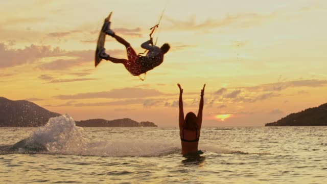 slo mo kitesurfer performing a jump in front of a woman - kiteboarding stock videos & royalty-free footage