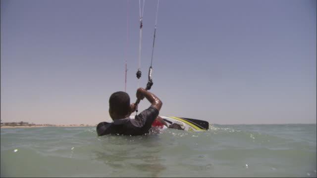 vidéos et rushes de a kitesurfer puts his feet into the bindings on the board and lets his parachute carry him away across the water. - harnais de sécurité