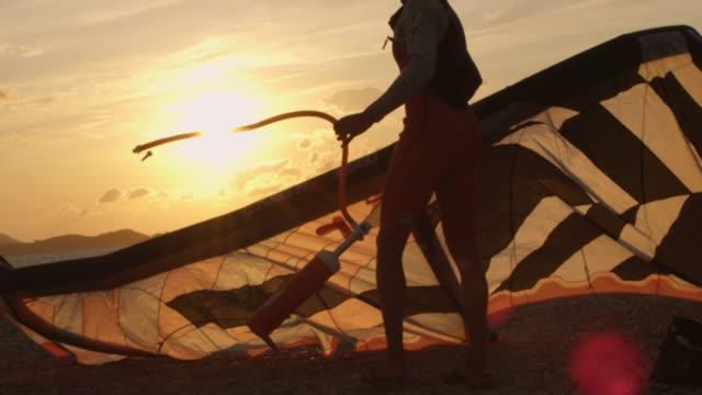 vídeos de stock, filmes e b-roll de slo mo kitesurfer definindo a pipa na praia - esporte aquático