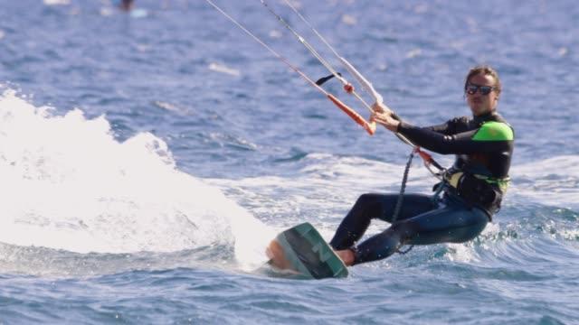 stockvideo's en b-roll-footage met slo mo kitesurfer surfen op de oceaan - windsurfen