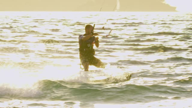 slo mo kitesurfer surfing over the waves of the sea - kiteboarding stock videos & royalty-free footage