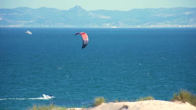 stockvideo's en b-roll-footage met kitesurfers surfing in the coast of spain near to africa - silvestre