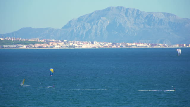 kitesurfers surfing in the coast of spain near to africa - kiteboarding stock videos & royalty-free footage