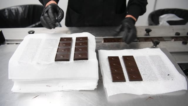 kiva confections cannabisinfused chocolate bars are arranged for wrapping at the company's headquarters in oakland california us on tuesday nov 2... - kivas stock videos & royalty-free footage