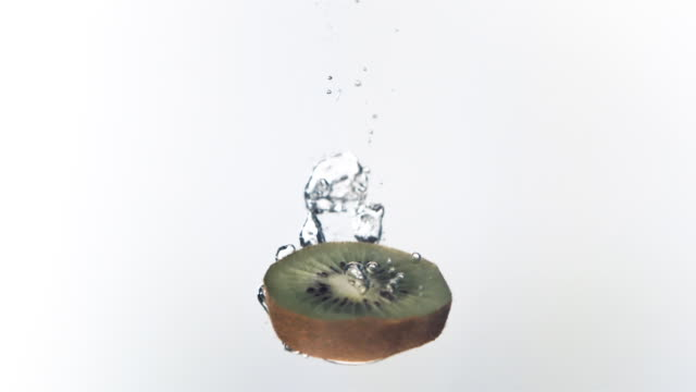 cu, slo mo, kiwi fruit falling into water liquid, studio shot - kiwi fruit stock videos and b-roll footage