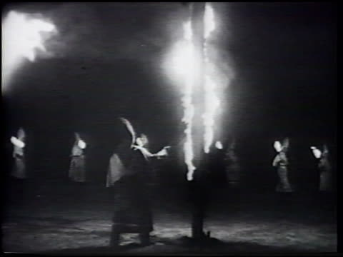 vídeos de stock, filmes e b-roll de klansmen in hooded robes walking circle w/ hooded person lighting christian cross on fire in center ws members throwing lighted torches into center... - ku klux klan