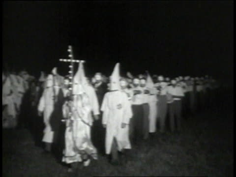 vídeos de stock, filmes e b-roll de klansmen in hoods marching / men in street clothes following / crowd raises burning cross - ku klux klan