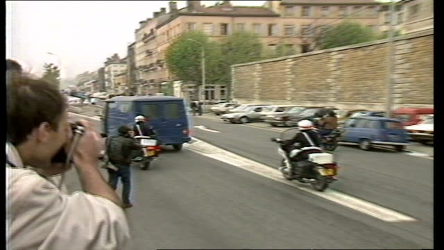 day 1; france: lyon: st joseph's prison tms small white van followed by blue prison van carrying klaus barbie out of prison gates towards with police... - crime or recreational drug or prison or legal trial stock-videos und b-roll-filmmaterial