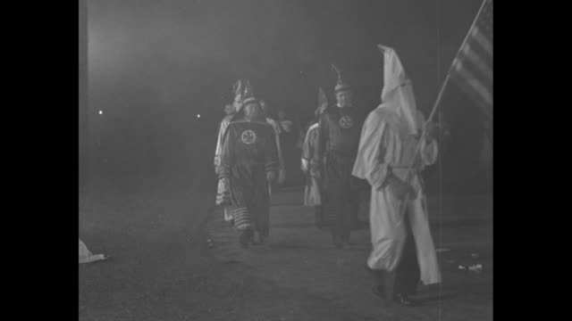 vídeos de stock, filmes e b-roll de klu klux klan rally at night / men in full hooded white sheet costume walking in a circle with burning cross / klan officials including imperial... - ku klux klan