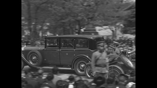 kneeling crowd members look on as they await arrival of emperor hirohito at yasukuni shrine for an homage to war dead / motorcade arrives / rear shot... - hirohito stock videos & royalty-free footage