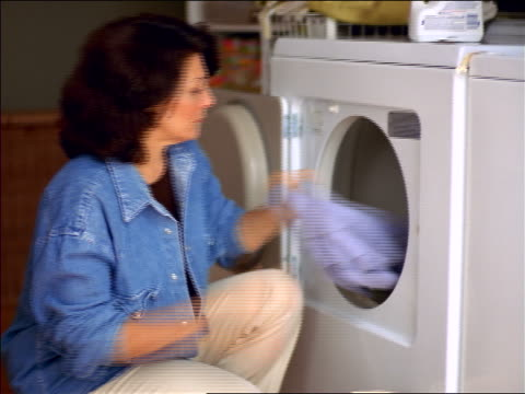 kneeling woman pulling clothing out of dryer - tumble dryer stock videos & royalty-free footage