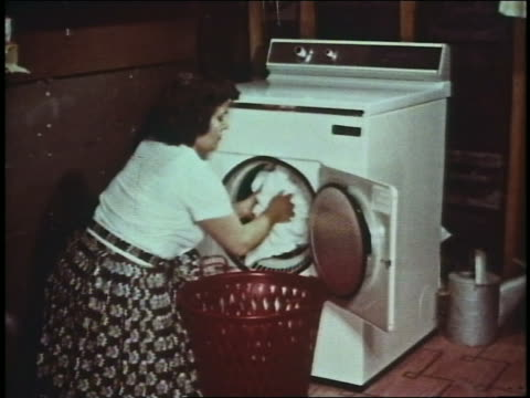 1960 kneeling woman unloading clothing from dryer into red laundry basket - 1960 stock videos & royalty-free footage