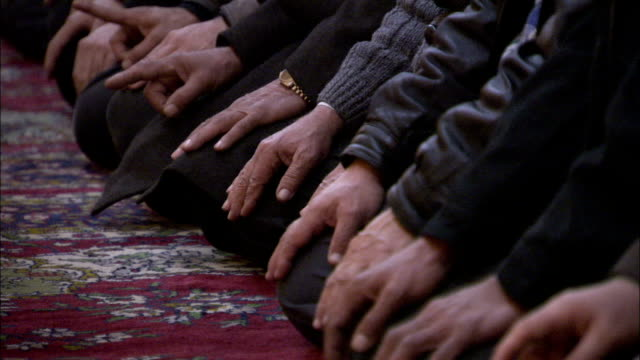 kneeling worshippers use finger signals during prayer in the umayyad mosque damascus. available in hd. - pregare video stock e b–roll
