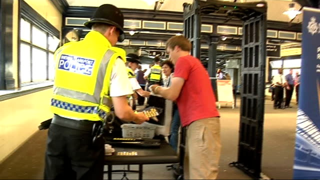 British Transport Police search commuters ENGLAND London INT Commuters pass through mobile metal detector arch at unidentified railway station...