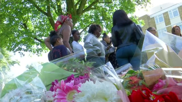 Family of murder victim Cheyon Evans pay tribute ENGLAND London Tooting EXT Low angle view floral tribute with bereaved family of stabbing victim...